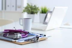 Estetoscopio, ordenador portátil, carpeta en el escritorio en hospital imagenes de archivo