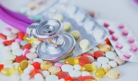 Estetoscopio, píldoras, frascos en sitio médico en maqueta azul de la opinión superior del fondo fotografía de archivo