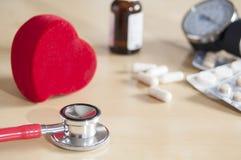 Estetoscopio rojo y coraz?n rojo en una tabla Cerca de las tabletas, de las cápsulas, de la botella de la medicina y del tonomete foto de archivo libre de regalías