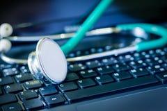 Estetoscopio sobre un teclado de ordenador portátil, datos del análisis del concepto de la salud imagen de archivo libre de regalías