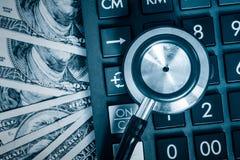Estetoscopio sobre una calculadora y billetes de dólar Imágenes de archivo libres de regalías