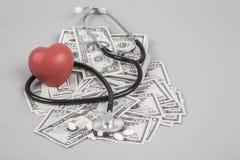 Estetoscopio y corazón rojo en dólares americanos Foto de archivo libre de regalías