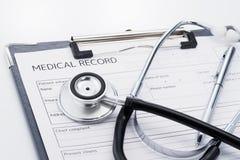 Estetoscopio y informe médico en el fondo blanco imagenes de archivo
