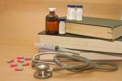 Estetoscopio y medicaciones en el libro Fotos de archivo