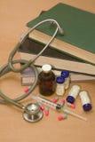 Estetoscopio y medicaciones en el libro Imagenes de archivo