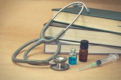 Estetoscopio y medicaciones en el libro médico Fotos de archivo libres de regalías