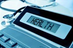 Estetoscopio y salud de la palabra en la exhibición de una calculadora fotografía de archivo libre de regalías