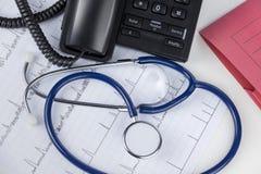 Estetoscopio y teléfono en un escritorio de los doctores Foto de archivo