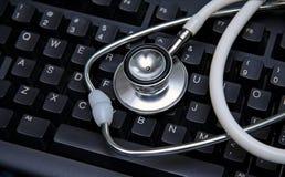 Estetoscópio em um teclado de computador Fotografia de Stock