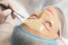 Esthéticien appliqué avec une masque de beauté de brosse Photographie stock