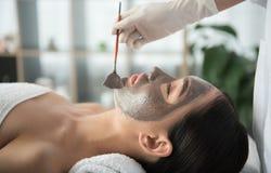 Esthéticien appliquant l'argile sur le visage femelle Images libres de droits