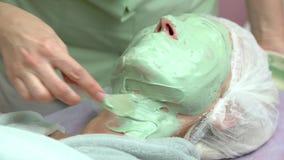 Esthéticien appliquant le masque de massage facial d'alginate banque de vidéos