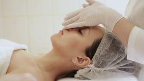 Esthéticien de docteur dans les gants blancs faisant le massage facial à une jeune femme banque de vidéos