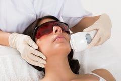 Esthéticien donnant le traitement de laser d'epilation photographie stock libre de droits
