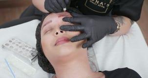 Esthéticien féminin exécutant une procédure du retrait de tatouage de sourcil sur un client banque de vidéos