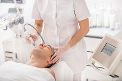 Esthéticien habile traitant le visage masculin par le laser Photo stock