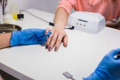 Esthéticien professionnel appliquant le vernis à ongles à l'ongle femelle Photos libres de droits