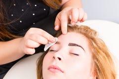 Esthetician Tidying Eyebrows des weiblichen Kunden Lizenzfreie Stockfotos