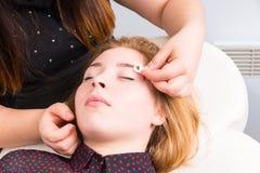 Esthetician Tidying Eyebrows des weiblichen Kunden Stockfotos