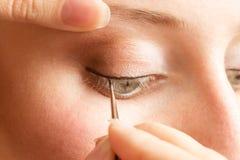 Esthéticien appliquant l'eye-liner sur la paupière Photographie stock