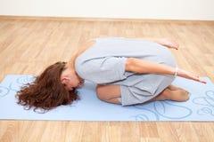 Esticado em poses praticando da ioga da mulher do assoalho Imagem de Stock