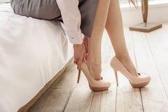 Estiletes vestindo da mulher bonita nos pés Fotografia de Stock Royalty Free