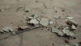 Estilhaços de vidro e de pedra no assoalho sujo na construção velha video estoque
