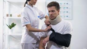 Estilingue paciente masculino do braço da fixação do ortopedista na posição direita, reabilitação após o traumatismo filme