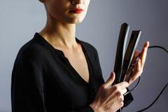Estilista da menina que guarda um ferro de ondulação para o cabelo fotografia de stock royalty free