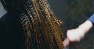 Estilista da mulher que penteia o cabelo Preparação do cabelo filme