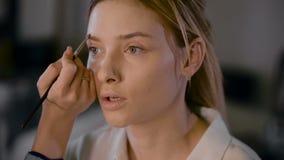 Estilista de la muchacha que trabaja en un estudio de la belleza Compense a un blonde hermoso Trabajo con la sombra metrajes