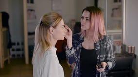 Estilista de la muchacha que trabaja en un estudio de la belleza Compense a un blonde hermoso Trabajo con la sombra almacen de metraje de vídeo