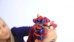 Estilista de sexo femenino que crea el peinado perfecto con los rizos grandes para la mujer joven del pelirrojo almacen de video