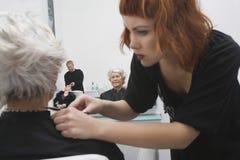 Estilista de sexo femenino que da corte de pelo al pelo de la mujer mayor Imágenes de archivo libres de regalías