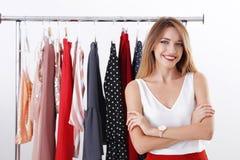 Estilista joven hermoso cerca del estante con ropa de diseñador imagen de archivo libre de regalías