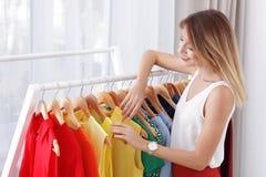Estilista joven hermoso que elige la ropa de moda del estante fotografía de archivo