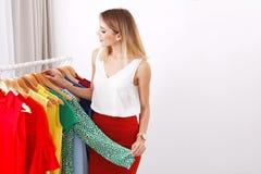 Estilista joven hermoso que elige la ropa de moda del estante fotografía de archivo libre de regalías