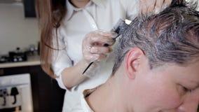Estilista joven, peluquero que aplica color del pelo a una mujer Coloración del cabello en el color oscuro, proceso almacen de video