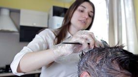Estilista joven, peluquero que aplica color del pelo a una mujer Coloraci?n del cabello en el color oscuro, proceso almacen de metraje de vídeo