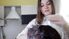 Estilista joven, peluquero que aplica color del pelo a una mujer Coloraci?n del cabello en el color oscuro, proceso metrajes