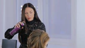 Estilista, peinado del acabamiento del peluquero para la mujer bonita joven metrajes