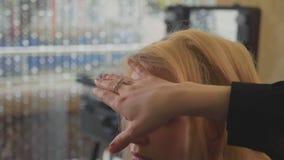 Estilista profissional que faz o penteado para a jovem mulher e que usa o pulverizador de cabelo video estoque
