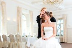 Estilista que fixa acima do penteado de uma noiva Fotografia de Stock