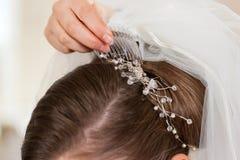 Estilista que fixa acima do penteado de uma noiva Fotos de Stock