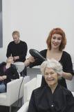 Estilista que hace el brushing el pelo de la mujer mayor en salón Imagen de archivo libre de regalías