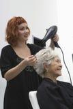 Estilista que seca o cabelo da mulher superior fotos de stock