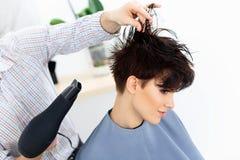 Estilista que usa el secador en el pelo mojado de la mujer en salón.  Pelo corto Fotos de archivo libres de regalías