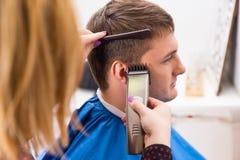 Estilista que usa a lâmina para cortar o cabelo do cliente masculino Imagens de Stock Royalty Free