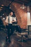 Estilista vestido con clase hermoso en una peluquería de caballeros Él es successf foto de archivo libre de regalías