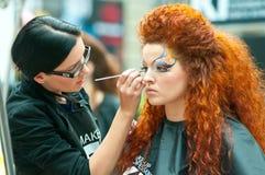 Estilista y modelo en la demostración para el maquillaje creativo Imagen de archivo